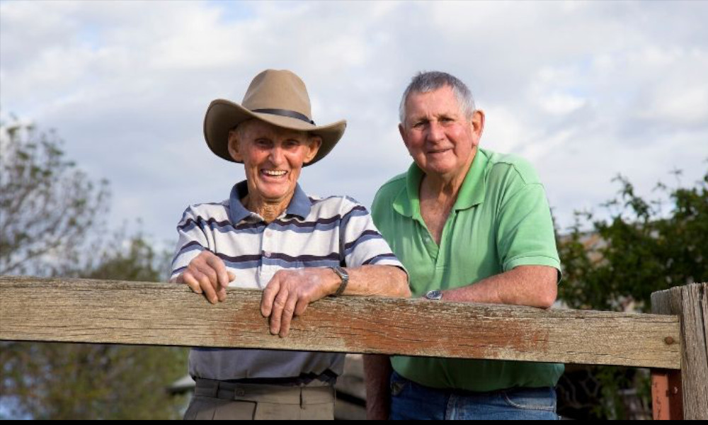 Two-men-standing-next-to-a-fence